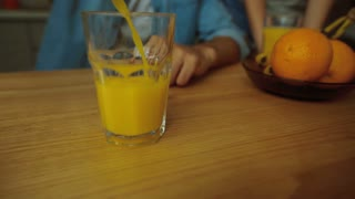 Pouring orange juice into glass shooting with high speed camera,