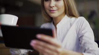 Pretty blonde having coffee while using tablet at the coffee shop, close-up