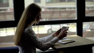 Pretty blonde in white shirt having a coffee using tablet pc at the coffee shop, side view