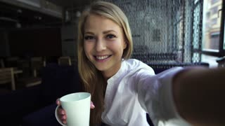 Pretty blonde woman taking self portrait while drinking coffee in a bar - Beautiful girl holding camera