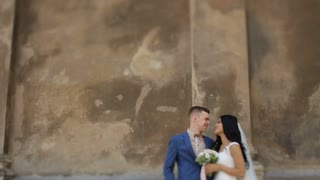 Pretty bride and handsome groom kissing on the street, near brown wall
