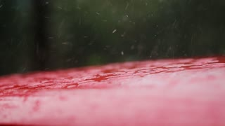 RAIN falls on the red hood MACHINES, raindrops dripping on it