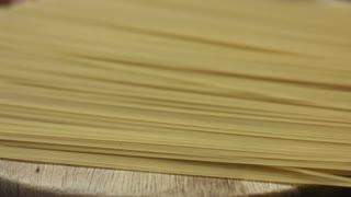 Raw bunch of spaghetti on a wooden board closeup