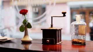 Red rose , vintage  coffee grinder mill with stylish clipping path and a glass bottle with luxury coffee inside on wooden board.