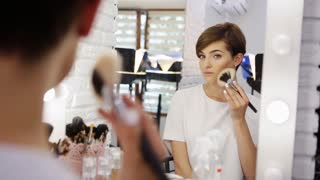 Reflection of young beautiful woman with short haircut applying her make-up, looking in a mirror