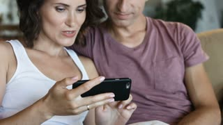 Relaxed married couple using a generic mobile phone together sitting on a sofa in the living room at home
