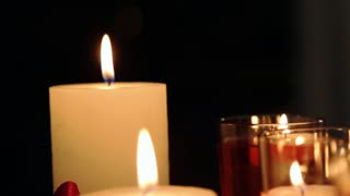 Romantic burning red and yellow candles over black background