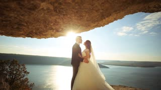 Romantic groom hugging his attractive young wife in a beautiful natural background.