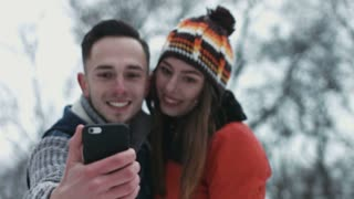 Romantic moment of a sweet couple making selfie while birds fly over the sky. Man and woman in their 20s taking pictures on mobile device outdoors in the winter.