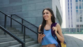 Satisfied fitness athlete using her smartphone. Sporty urban woman in blue top and with sports bag, close-up