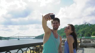 Selfie - Happy sporty couple taking self portrait photo at the bridge. Two friends or lovers on morning training smiling at camera outdoors