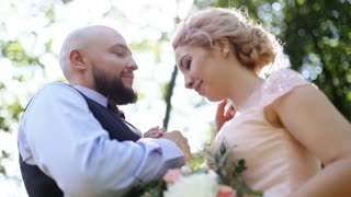 Sensual close up portrait of handsome groom kissing forehead of his beautiful bride, outdoors