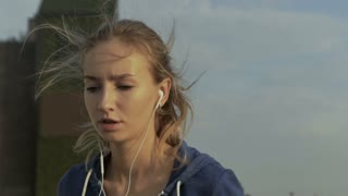 Serious young woman listening to music in her earphones, while running near the sea.