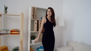 Sexy brunette business woman in fashionable black dress standing in light office
