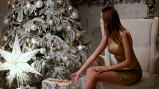 Sexy young woman wearing beautiful dress, sitting on a chair and opening her gift.