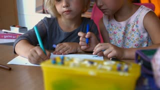 Siblings drawing with colored pencils while sitting at desk at home in nursery