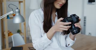 Side view of attractive smiling brunette female photographer in white shirt checking an image holding her camera, office interior at background.