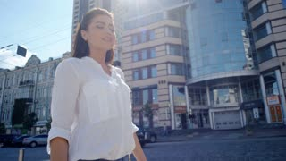 Side view of beautiful woman in white shirt and with dark long hair walking through urban city streets