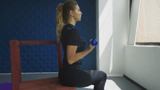 Side view of confident young woman with blue dumbbells at fitness studio