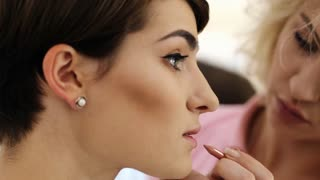 Side view of makeup artist applying with pink pencil cosmetic on lips of her young client with short dark haircut