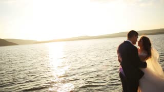 Silhouette of a loving happy couple hugging on the background of the setting sun .