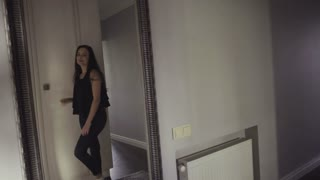 Slow motion footage how cheerful and happy girl spins before a mirror.