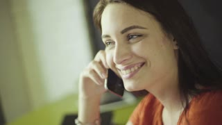 Slow motion footage how young brunette woman talking on telephone and smiling.