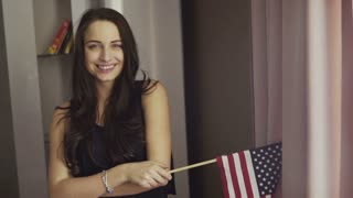 Slow motion footage of a girl stands in a living room, makes a  cherful smile and hold a flag of the United States.