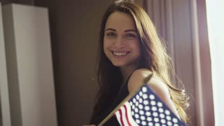 Slow motion footage of a model holds an american flag indoors and makes poses.