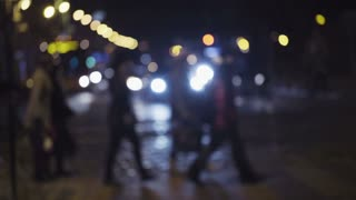 Slow motion footage of night traffic in a city center. Pedestrians cross the street on a crosswalk. Blurred image of people crossing the road.