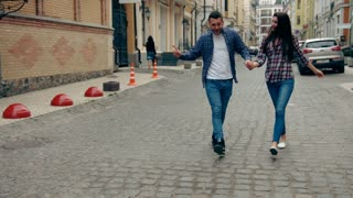 Slow motion shot of young couple dancing along street towards camera.