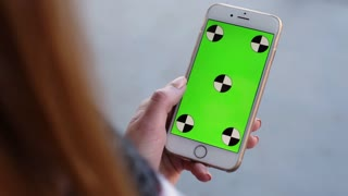 Smart Phone held by woman hands. Green screen Chroma Key. Close up. Tracking motion. Vertical. White background. 6