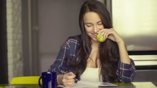 Smiling beautiful young woman sitting writing in her dining room at the table holding green apple as healthy snack