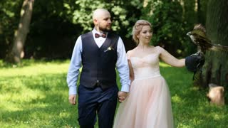 Smiling bridal couple with eagle at green forest walking holding hands