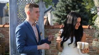 Smiling brunette bride putting wedding ring on groom during outdoors wedding ceremony