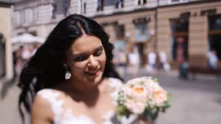 Smiling brunette bride with bright face looking up walking on the street in a sunny day