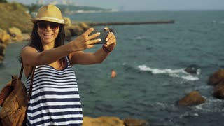 Smiling cute tanned woman taking selfies, while staying on the stone near blue calm sea.
