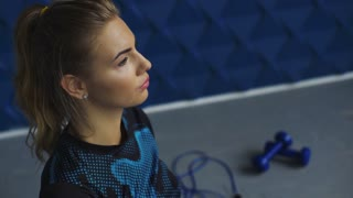 Smiling eyes. Close up portrait of young pretty smiling blond-haired woman resting after training in gym