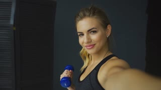 Smiling sporty girl doing dumbbell curls and using app on mobile phone, taking picture, selfie, self-portrait with smartphone