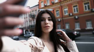 Smiling woman taking a self photo in urban street. Beautiful caucasian brunette girl in white jacket with makes selfie. A tourist.