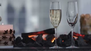 Sparkling champagne wine in glasses in front of the warm fireplace. Close up