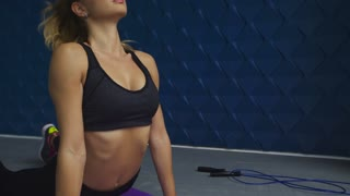 Sports girl on mat doing back exercises, training in the gym