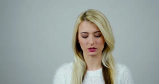 Stand-up studio footage of a blonde woman makes expressions of laugh