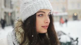Street emotional portrait of young beautiful woman in city Model looking at camera. Lady wearing stylish classic winter knitted clothes. Christmas concept. Snowfall
