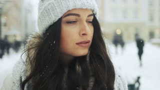 Street emotional portrait of young beautiful woman in city Model looking at camera. Lady wearing stylish classic winter knitted clothes -winter holidays, christmas, beverages and people concept