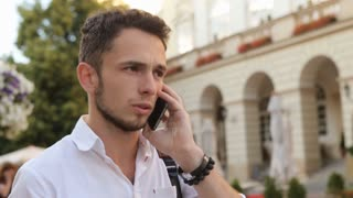 Student have a conversation on mobile phone. Close-up portrait of a man talking on cellphone in slow motion.