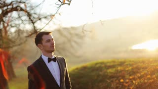 stylish brunette smiling groom in a suit with a brown bow holds  walking autumn park     shot in slow motion  close up