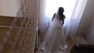 Stylish luxury gorgeous brunette bride posing near window on the background hotel room. Bride with bouquet. Top view.
