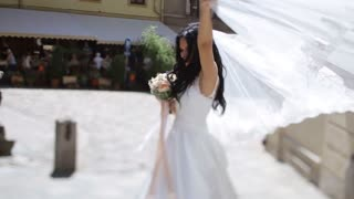 Stylish woman in white dress and veil dancing in the street of old city