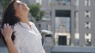 Successful brunette businesswoman in white shirt and with blowing long hair looking up next to her office building